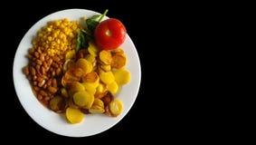 Зажаренные картошки, томат, фасоли и мозоль на белой плите с неровными краями Черная предпосылка стоковое изображение rf