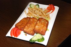 Зажаренные котлеты рыб с французскими картофелем фри и овощами на белой плите стоковые фотографии rf