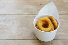 Зажаренные кольца лука в чашке на деревянном столе Стоковое Изображение