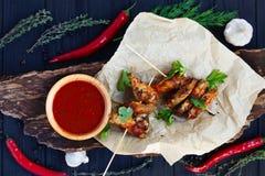 Зажаренные крыла цыпленка с пряным томатным соусом на ремесле завертывают ser в бумагу стоковое фото rf