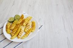 Зажаренные куски ананаса с известкой на белой плите над белой деревянной предпосылкой, взглядом со стороны Еда лета Идея для заку Стоковые Изображения RF