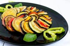 Зажаренные куски цукини, баклажан, томат на черной плите на белой предпосылке Стоковая Фотография