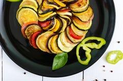 Зажаренные куски цукини, баклажан, томат на черной плите на белой предпосылке Стоковые Изображения