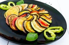 Зажаренные куски цукини, баклажан, томат на черной плите на белой предпосылке Стоковые Фотографии RF
