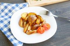 Зажаренные клин картошки с томатом вишни Стоковое Фото