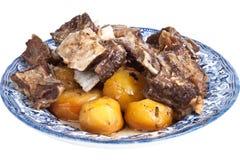 Зажаренные мясо и картошки на плите изолированной на белой предпосылке Стоковые Изображения RF