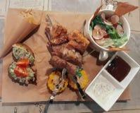Зажаренные мясо и овощи, салат и соусы барбекю на ремесле завертывают предпосылку в бумагу Стоковые Фотографии RF