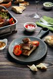 Зажаренные нервюры и сосиски свинины, который служат с томатом и соусами на деревянном столе стоковая фотография rf