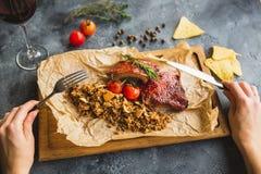 Зажаренные нервюры свинины, гречиха с грибом и томаты на винтажных деревянных руках разделочной доски и женщины с столовым прибор Стоковая Фотография RF