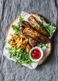Зажаренные нервюры свинины и французский картофель фри на деревянной доске на серой предпосылке Очень вкусный обед, закуски, тапы стоковая фотография rf