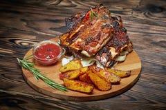 Зажаренные нервюры с розмариновым маслом, картошки деревенские, лук, соус на деревянной круглой доске стоковые фотографии rf