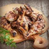 Зажаренные ноги цыпленка на разделочной доске Деревенская предпосылка обедающего Стоковое Фото