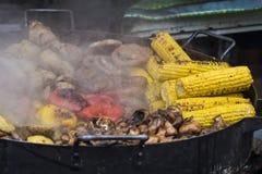 Зажаренные овощи и деликатесы мяса проданные outdoors на рыночном мести местного рынка стоковые фото