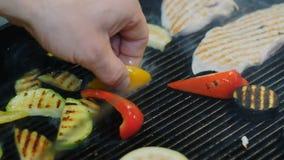 Зажаренные овощи, филе цыпленка, варящ мясо и овощи на гриле Рука, используя шпатель для того чтобы повернуть мясо в акции видеоматериалы