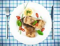 Зажаренные рыбы на белых плите и вилке, ноже Стоковое Фото