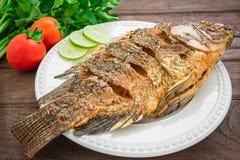 Зажаренные рыбы на плите с овощами Стоковое Изображение RF