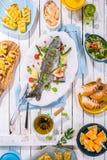Зажаренные рыбы на таблице с другими блюдами Стоковые Изображения