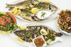 Зажаренные рыбы с кусками лимона, зажаренные морепродукты служили на плите изолированной на белизне Стоковое Фото