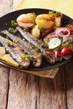 Зажаренные сардины с зажаренными в духовке картошками и свежим крупным планом салата Стоковое Изображение