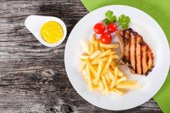 Зажаренные свиные отбивние на белом блюде с французскими фраями Стоковое Изображение RF