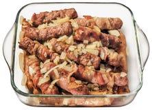 Зажаренные семенить хлебцы мяса Cevapcici с прерванным луком в стеклянном лотке выпечки изолированном на белой предпосылке Стоковые Изображения