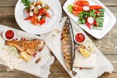 Зажаренные скумбрия и морской окунь свежие овощи салата Служение на деревянной доске на деревенской таблице Барбекю Стоковые Фотографии RF