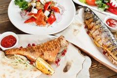 Зажаренные скумбрия и морской окунь свежие овощи салата Служение на деревянной доске на деревенской таблице Барбекю Стоковое фото RF