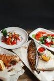 Зажаренные скумбрия и морской окунь свежие овощи салата Служение на деревянной доске на деревенской таблице Барбекю Стоковая Фотография RF