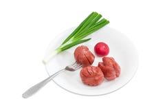 Зажаренные сосиски, вилка, зеленый лук, красная редиска на белом блюде Стоковое Фото