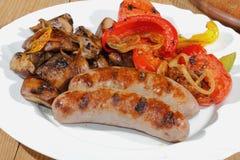 Зажаренные сосиски, грибы, томаты, перцы стоковое фото