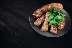 Зажаренные сосиски мяса с овощами и петрушкой на плите Стоковые Фото