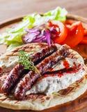 Зажаренные сосиски мяса с погружением хлеба питы и салата и tzatziki овощей стоковое фото