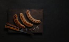 Зажаренные сосиски на черной деревянной доске Стоковые Изображения