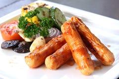 Зажаренные сосиски сыра с зажаренными в духовке овощами на белом блюде Стоковое фото RF