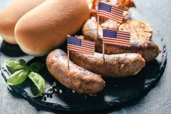 Зажаренные сосиски с американскими флагами Стоковые Изображения
