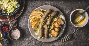 Зажаренные сосиски с испеченными яблоками, луками и здравицей плюшки отзола служили на деревенской таблице с белым салатом colesl Стоковое фото RF