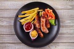 Зажаренные сосиски с фраями Сосиски с картошками и овощами Стоковые Фотографии RF