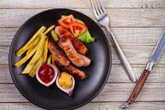 Зажаренные сосиски с фраями Сосиски с картошками и овощами Стоковое фото RF