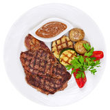 Зажаренные стейки, испеченные картошки и овощи на белой плите дальше стоковые фото