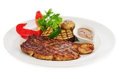 Зажаренные стейки, испеченные картошки и овощи на белой плите стоковое изображение rf