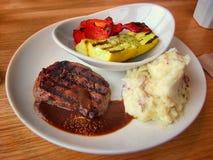 Зажаренные стейк, картофельные пюре чеснока и овощи на белой плите на ресторане Стоковое Изображение RF