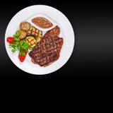 Зажаренные стейк, картошки и овощи на черной предпосылке стоковое изображение