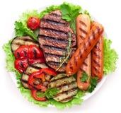 Зажаренные стейк, сосиски и овощи. стоковые изображения