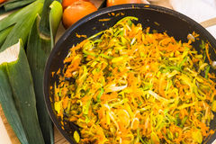 Зажаренные лук-порей и морковь в лотке на деревянной доске Стоковые Фотографии RF