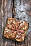 Зажаренные хлебцы мяса Cevapcici и бедренные кости цыпленка с прерванным луком в стеклянном комплекте лотка выпечки на старой тре Стоковое Фото