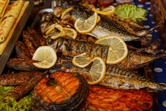 Зажаренные части рыб с кусками лимона на таблице Стоковые Фотографии RF