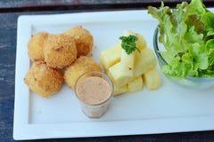 Зажаренные шарики и салат картошек на деревянной таблице Стоковые Фото