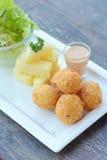 Зажаренные шарики и салат картошек на деревянной таблице Стоковые Изображения