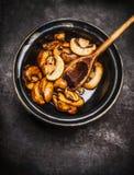 Зажаренные champignons в шаре с варить ложку на темной деревенской предпосылке Стоковые Фотографии RF