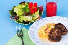 Зажаренный бургер с салатом картошки на плите, частью салата салата и питьем на голубой таблице Стоковые Изображения RF